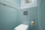 Две стены и пол выложены бело-голубым кафелем большого формата, центральная стена дополнительно декорирована мозаичной плиткой